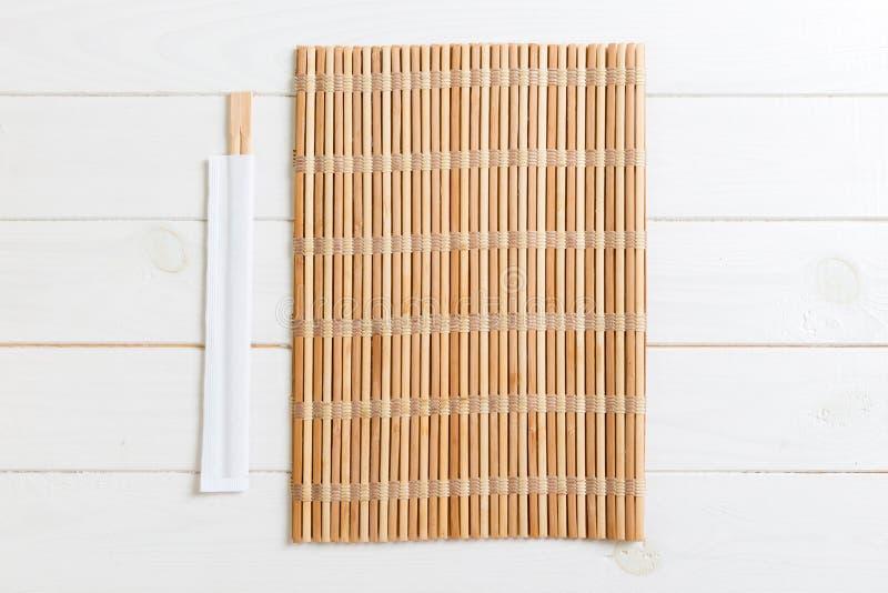 Twee sushieetstokjes met leeg bamboemat of hout plateren op houten Achtergrond Hoogste mening met exemplaar stace stock afbeelding