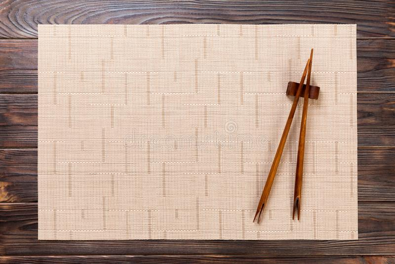Twee sushieetstokjes met leeg bruin bamboemat of hout plateren op houten Achtergrond Hoogste mening met exemplaarruimte leeg Azia stock afbeelding