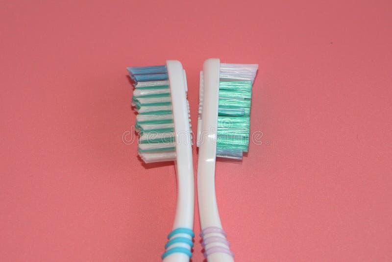 Twee tandenborstels op een roze achtergrond Mondelinge hygiëne stock afbeeldingen