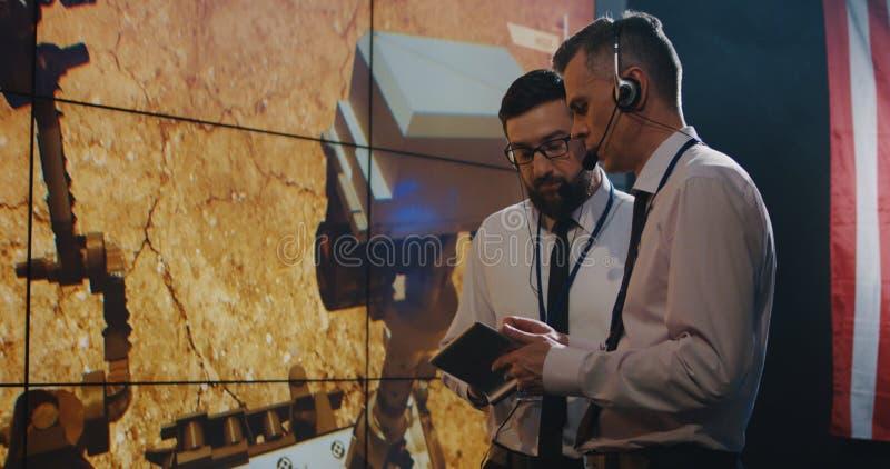 Twee technici die op het scherm in controlekamer letten royalty-vrije stock fotografie