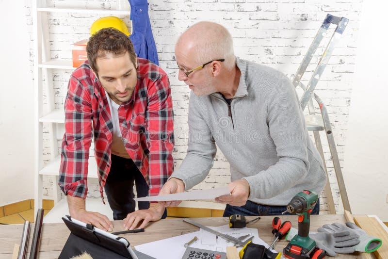 Twee technici gelezen plan in de workshop stock afbeelding