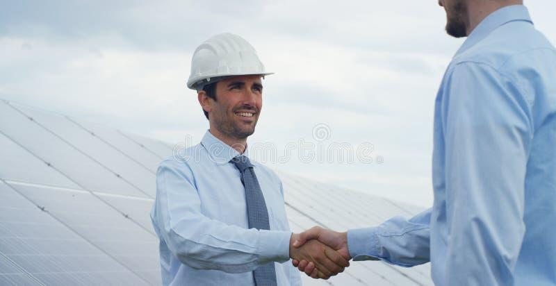 Twee technische deskundigepartners in zonne photovoltaic panelen, afstandsbediening voert routinehandelingen uit om systeem het g royalty-vrije stock afbeelding