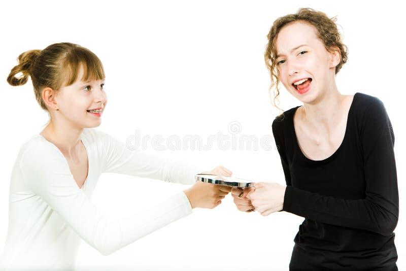 Twee teenaged meisjes, met steunen, in puberteitleeftijd kibbel om een spiegel ertoe te brengen om een merk omhoog te maken - zus royalty-vrije stock fotografie