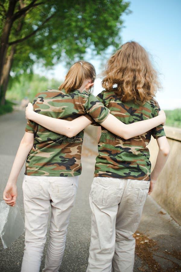 Twee teenaged vrienden in camouflaget-shirts royalty-vrije illustratie