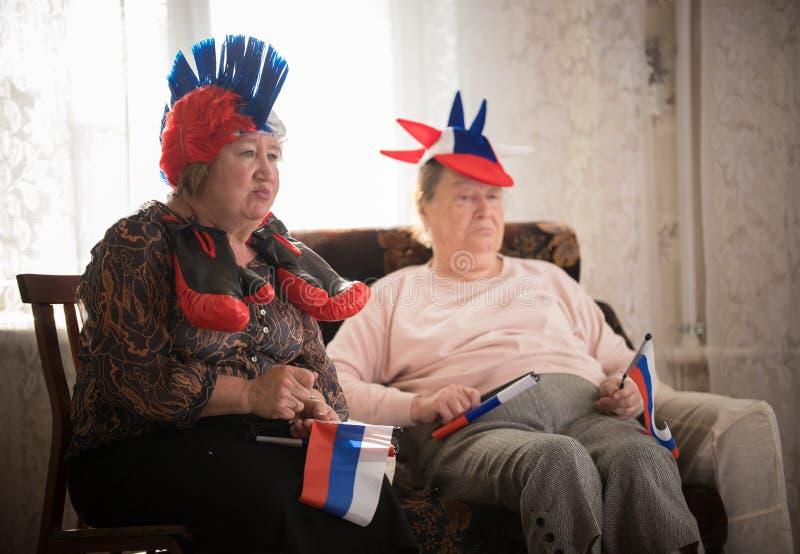 Twee teleurgestelde bejaarden die op TV in Russische toebehoren letten royalty-vrije stock afbeelding