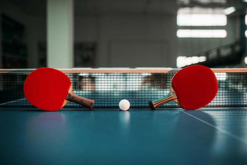 Twee tennisrackets en bal tegen netto op lijst stock fotografie
