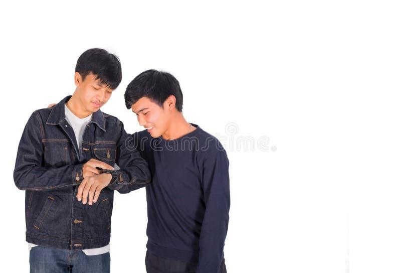 Twee Thaise jongens in jeansjasje bekijken het horloge royalty-vrije stock fotografie