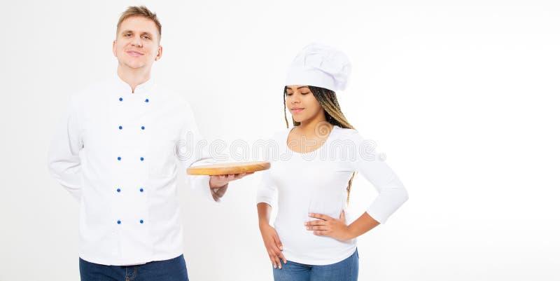 Twee tienerchef-koks die een lege pizzaraad houden die op wit wordt geïsoleerd Wit en afro Amerikaanse kooktoestellen in eenvormi royalty-vrije stock afbeeldingen