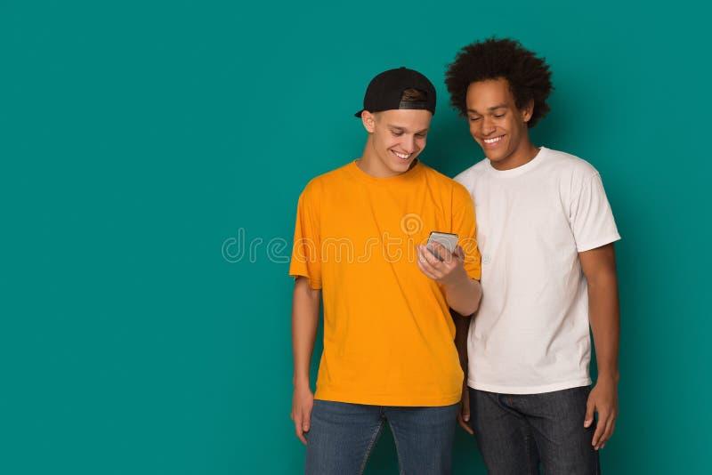 Twee tienerkerels die smatphone op blauwe achtergrond gebruiken royalty-vrije stock fotografie