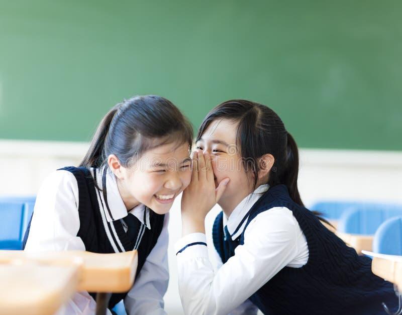 Twee tienermeisjes die in klaslokaal roddelen stock afbeeldingen
