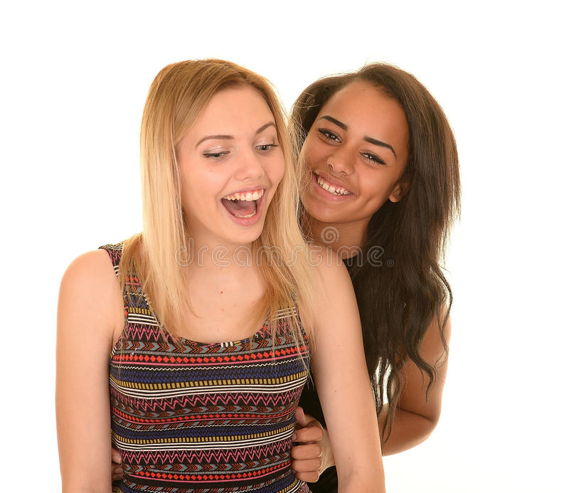 Twee Tienermeisjes die op Witte Achtergrond lachen stock foto
