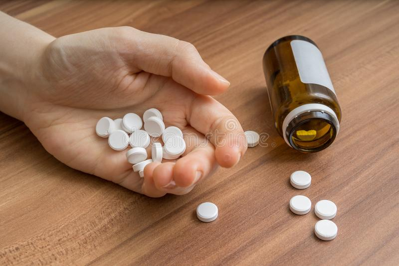 Twee tienermeisjes in openlucht Hand van persoon die heel wat pillen nam stock foto