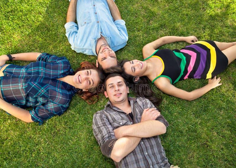 Twee tienerparen die op het gras ontspannen stock foto