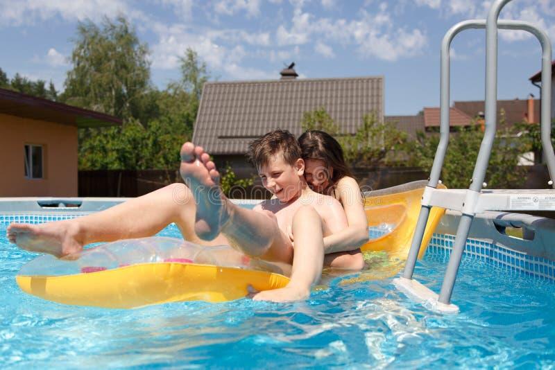 Twee tieners die in de pool zwemmen stock fotografie