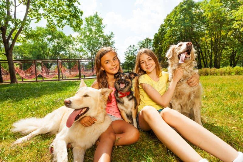 Twee tieners die met drie honden in park zitten royalty-vrije stock afbeeldingen