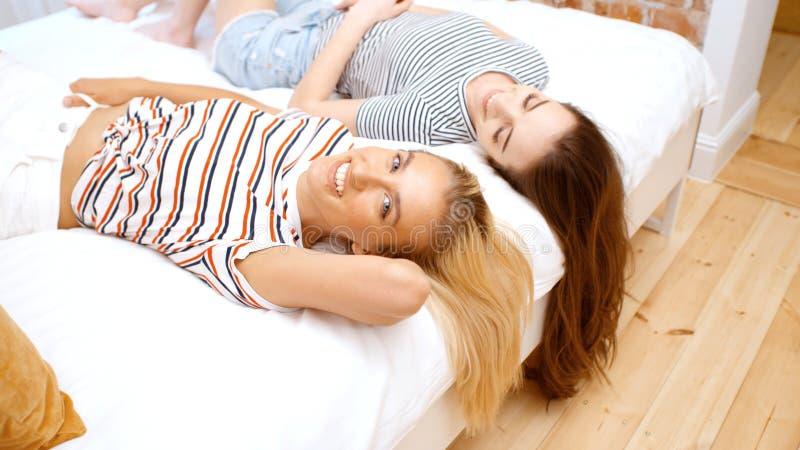 Twee tieners die op bed in comfortabele ruimte liggen en pret hebben royalty-vrije stock afbeelding