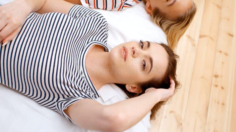 Twee tieners die op bed in comfortabele ruimte liggen en pret hebben royalty-vrije stock afbeeldingen