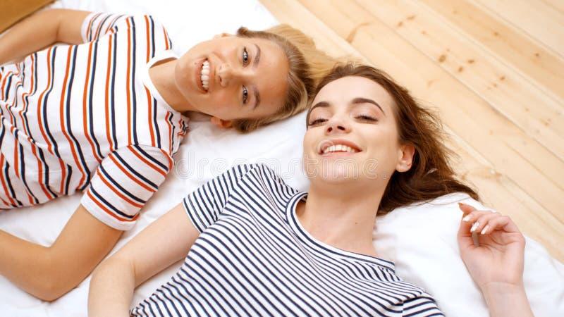 Twee tieners die op bed in comfortabele ruimte liggen en pret hebben stock foto's