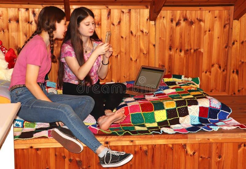 Twee tieners die op het bed zitten die de mobiele telefoon bekijken royalty-vrije stock fotografie