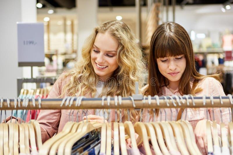 Twee tieners die voor kleren winkelen stock afbeelding