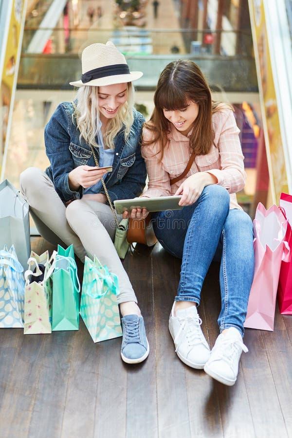 Twee tieners gebruiken tablet voor online het winkelen stock afbeelding