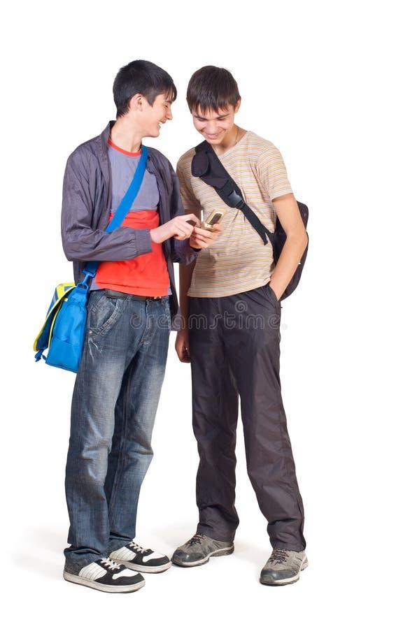 Twee tieners overwegen telefoon stock afbeeldingen