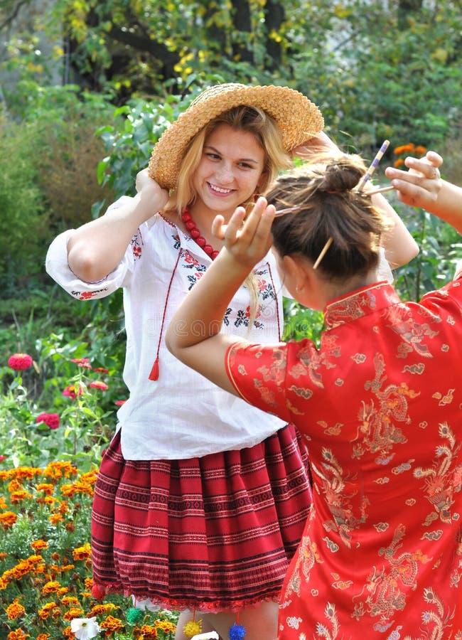 Twee tieners in traditionele Oekraïense en Chinese kleren royalty-vrije stock foto