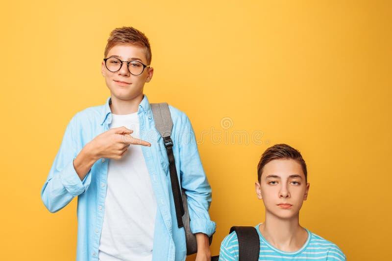 Twee tienervrienden, één kerel vernedert andere, populair vernedert impopulair, op een gele achtergrond royalty-vrije stock foto's