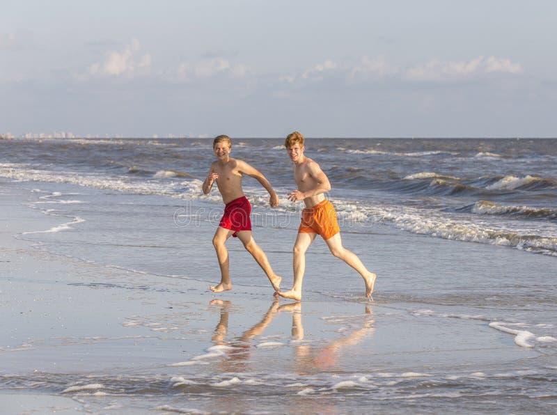 Twee tienervrienden en broers genieten van aanstotend langs het strand royalty-vrije stock foto