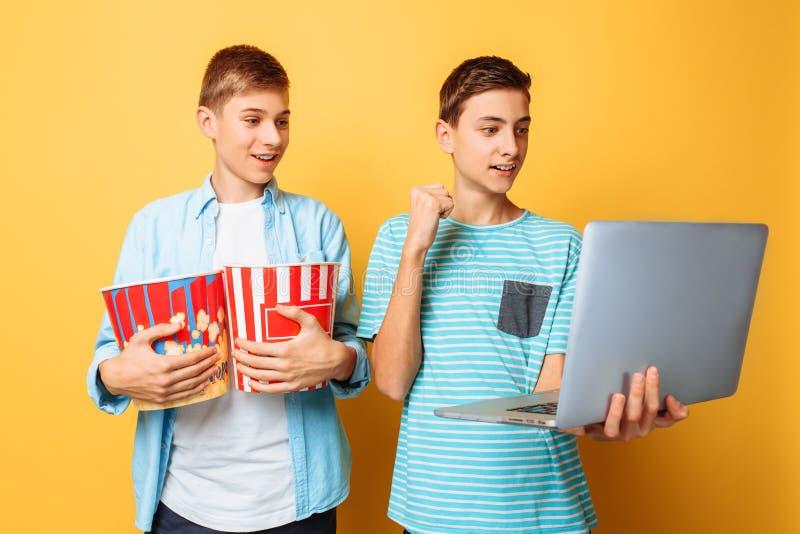 Twee tienervrienden met een emmer van popcorn in hun handen en laptop die op films op een gele achtergrond voorbereidingen treffe stock afbeeldingen