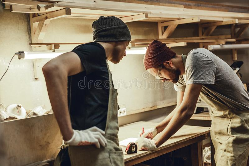 Twee timmerlieden die schetsen op werkbank maken stock afbeelding