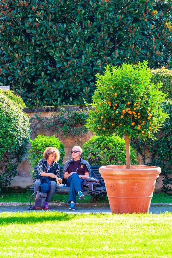 Twee toeristen, man en vrouw, paar, zitting en het rusten op de bank dichtbij de citrusboom in Vierkante Tuin in Vatikaan royalty-vrije stock afbeeldingen