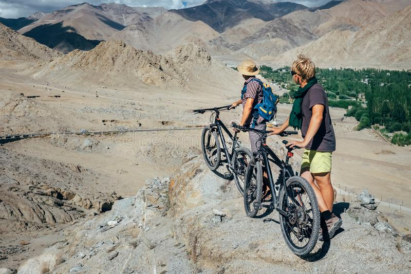 Twee toeristen met fietsen onderzoeken de berggebied van Himalayagebergte royalty-vrije stock afbeelding