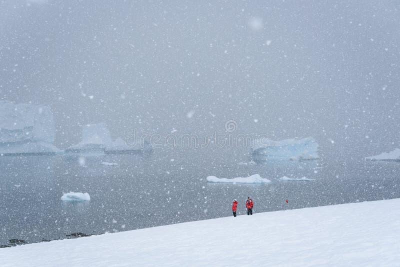 Twee toeristen in rode lagen op snowfield, die hard natte zware sneeuw, water en ijsbergen in een mistig Eiland achtergrond van D stock foto's