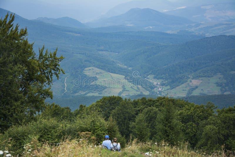 Twee toeristenmeisjes zitten op de berghelling stock foto's