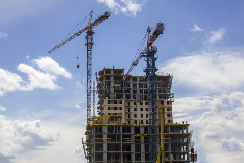 Twee torenkranen bovenop een wolkenkrabber in aanbouw met arbeiders tegen een blauwe hemel met wolken stock afbeeldingen