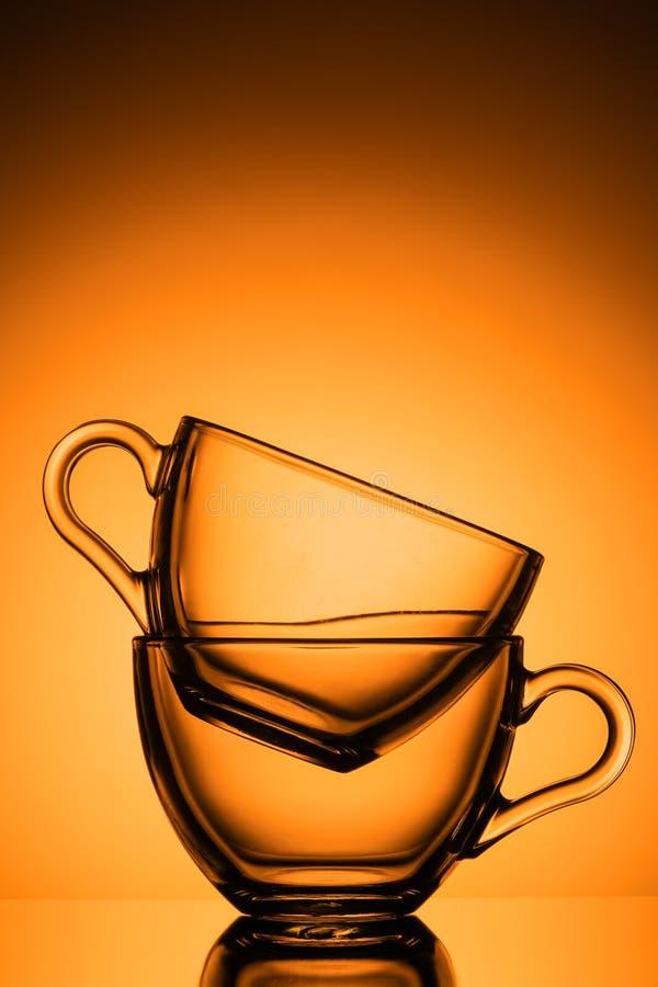 Twee transparante glasmokken voor thee Oranje achtergrond, close-up, verticaal schema stock afbeelding