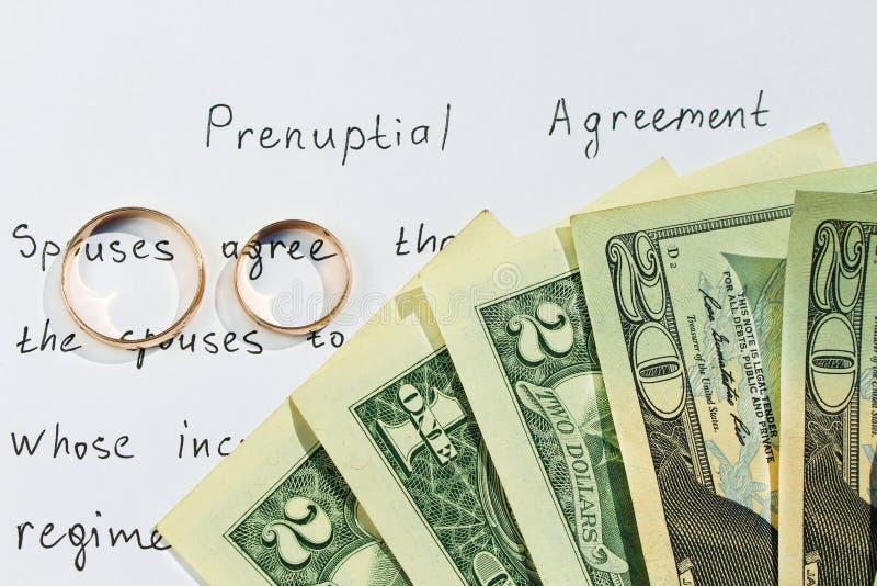 Twee trouwringen, dollars op achtergrond van huwelijkscontract stock afbeelding