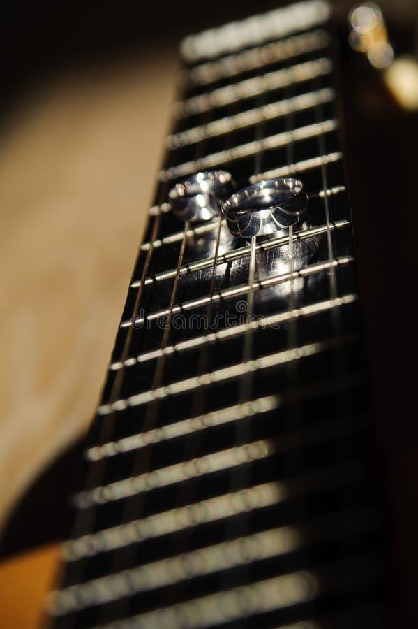 Twee trouwringen liggen op de koorden van een gitaar royalty-vrije stock foto's