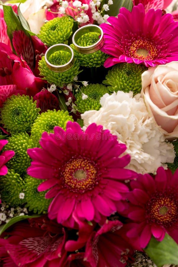 Twee trouwringen op een bruids kleurrijk boeket stock afbeeldingen