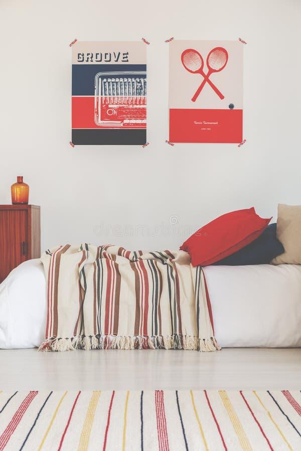 Twee uitstekende affiches boven enig comfortabel bed met gestreept deken en tapijt, echte foto royalty-vrije stock afbeelding