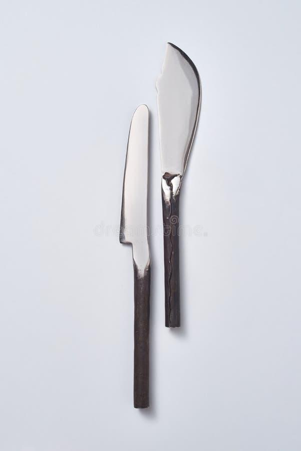 Twee uitstekende die messen op een grijze achtergrond met exemplaarruimte worden voorgesteld voor tekst Vlak leg stock foto