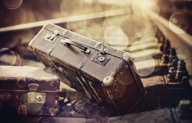 Twee uitstekende koffers liggen op spoorwegsporen stock fotografie