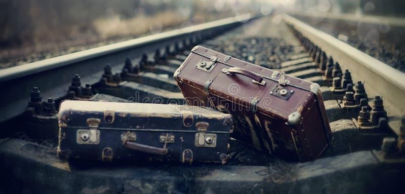 Twee uitstekende koffers liggen op spoorwegsporen royalty-vrije stock afbeeldingen