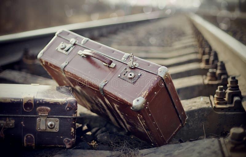 Twee uitstekende koffers op sporen stock fotografie