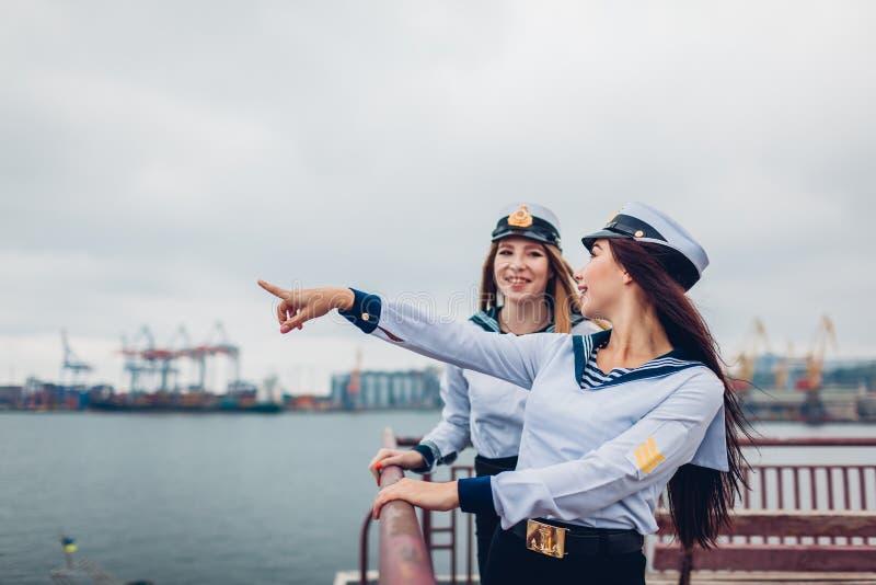 Twee universiteitsstudentes die van Mariene academie door overzeese eenvormig te dragen lopen Vrienden die in afstand op pijler r royalty-vrije stock fotografie