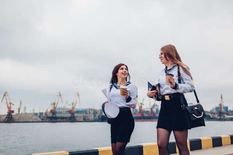Twee universiteitsstudentes die van Mariene academie door overzeese eenvormig te dragen lopen Vrienden die en in afstand lopen ri stock afbeelding