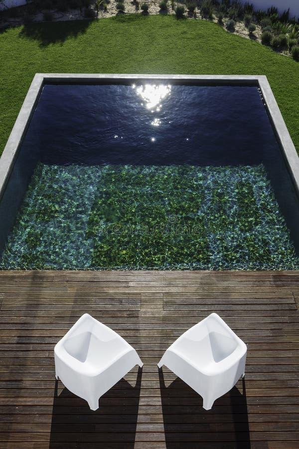Twee van het tuinstoelen en zwembad mening en houten dek royalty-vrije stock fotografie