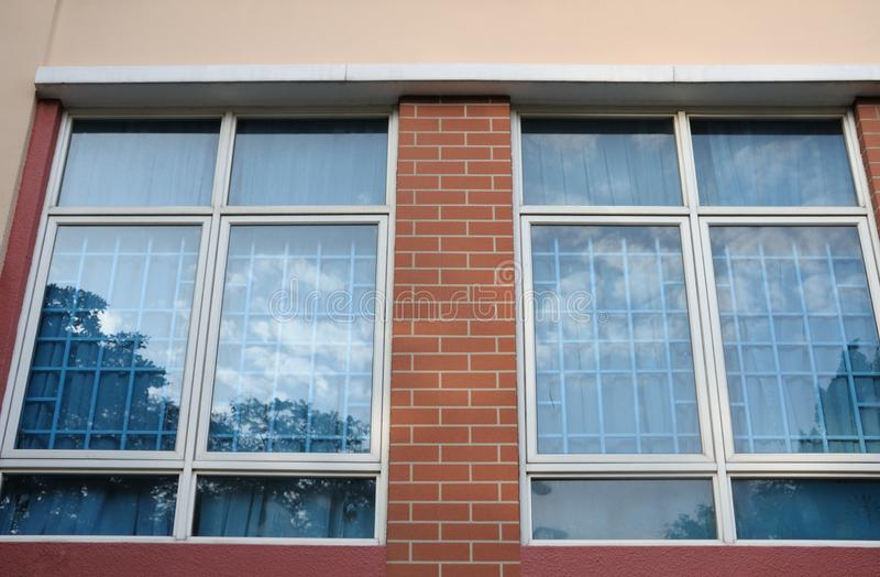 Twee vensters met bezinning van de azuurblauwe blauwe hemel op de glasruiten royalty-vrije stock fotografie