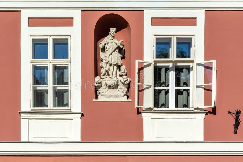 Twee vensters met een beeldhouwwerk stock foto's